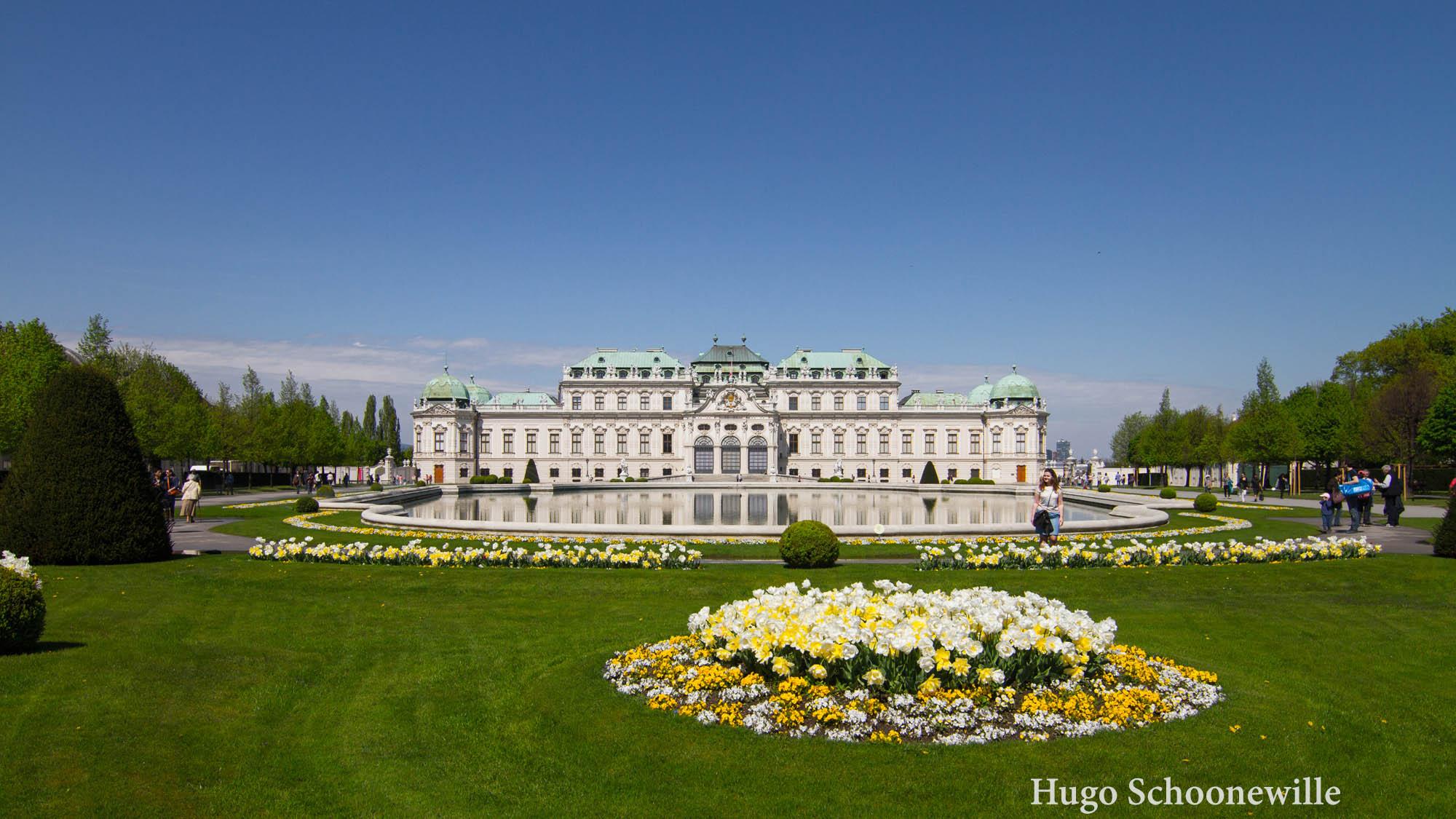 Schloss Belvedere met het meer ervoor op een zonnige dag met veel bloemen eromheen.