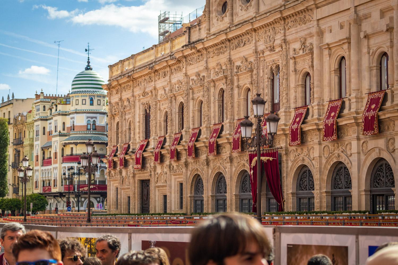 Bezienswaardigheden in Sevilla: het stadhuis van Sevilla tijdens Semana Santa, versierd met het stadswapen op rode banieren