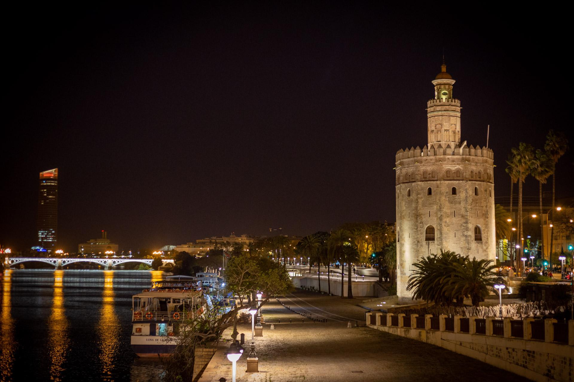 Verlichte Torre del Oro langs de Gudalquivir in Sevilla in de avonduren