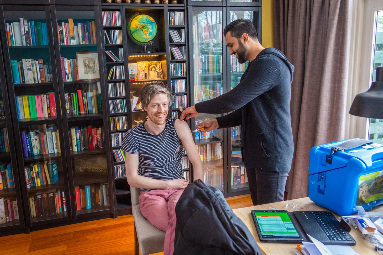 Hugo zit op een stoel en krijgt een reisvaccinatie via Thuisvacicnatie.nl in de woonkamer