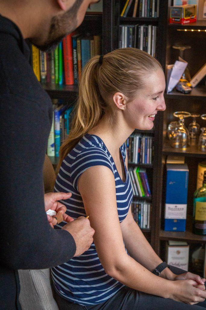 Manouk krijgt een reisvaccinatie in de woonkamer van een medewerker van Thuisvaccinatie.nl