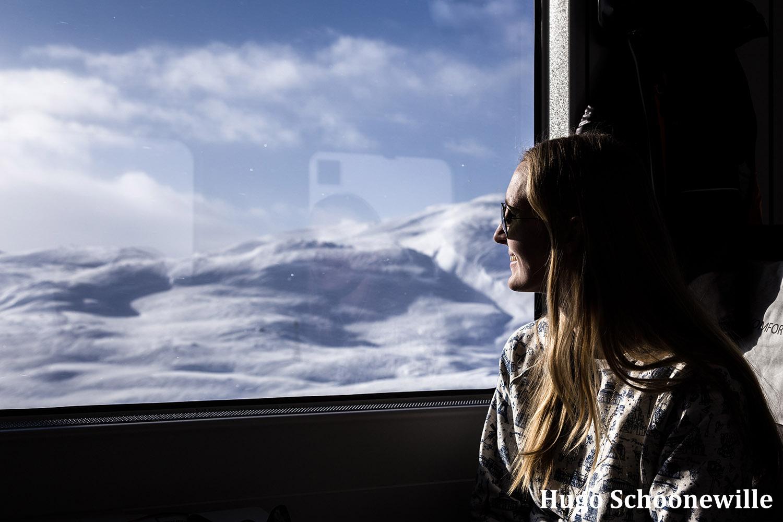 Blonde vrouw kijkt uit het raam tijdens de Bergensbanen treinreis.