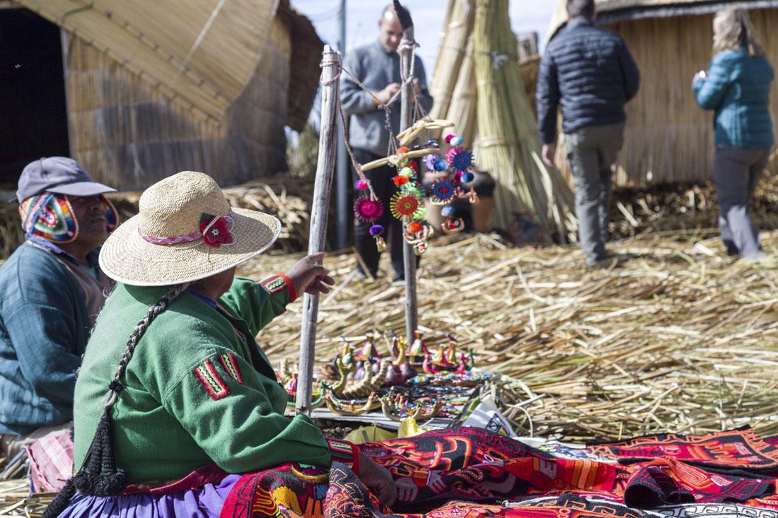 Vrouw met zelfgemaakte spullen op de rieteilanden Uros in het Titicacameer.