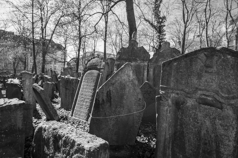 Joodse begraafplaats in Praag: scheve, oude grafstenen van de opeengestapelde graven. Zwart-witfoto.
