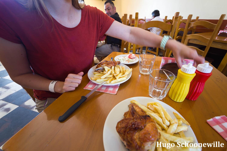 Kip met frietjes op borden op tafel bij restaurant Rico Pollo