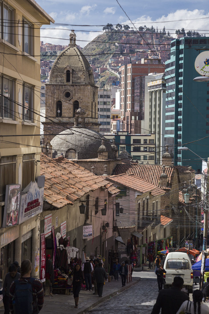 Aflopend straatje in La Paz, vol terracotta huizen en met bergen op de achtergrond.