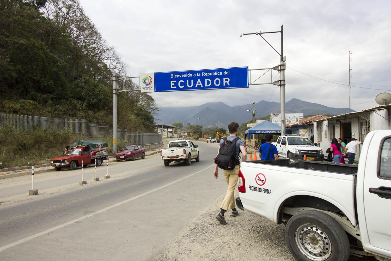 Hugo staat naast een witte jeep bij de grensovergang tussen Peru en Ecuador