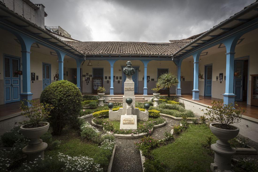 De groene binnenplaats van Museo de La Musica in Loja met blauwe pilaren rondom