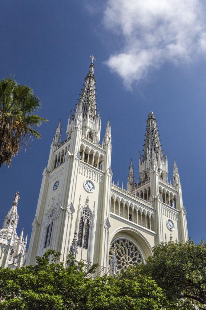 De witte torens van de De kathedraal van Guayaquil boven de groene struiken van het park