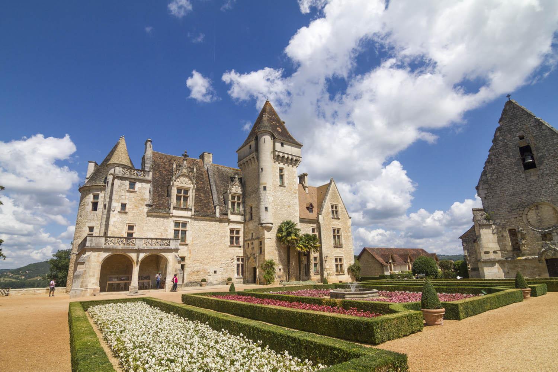 Chateau Milandes met een bloemenperk ervoor tegen een blauwe lucht