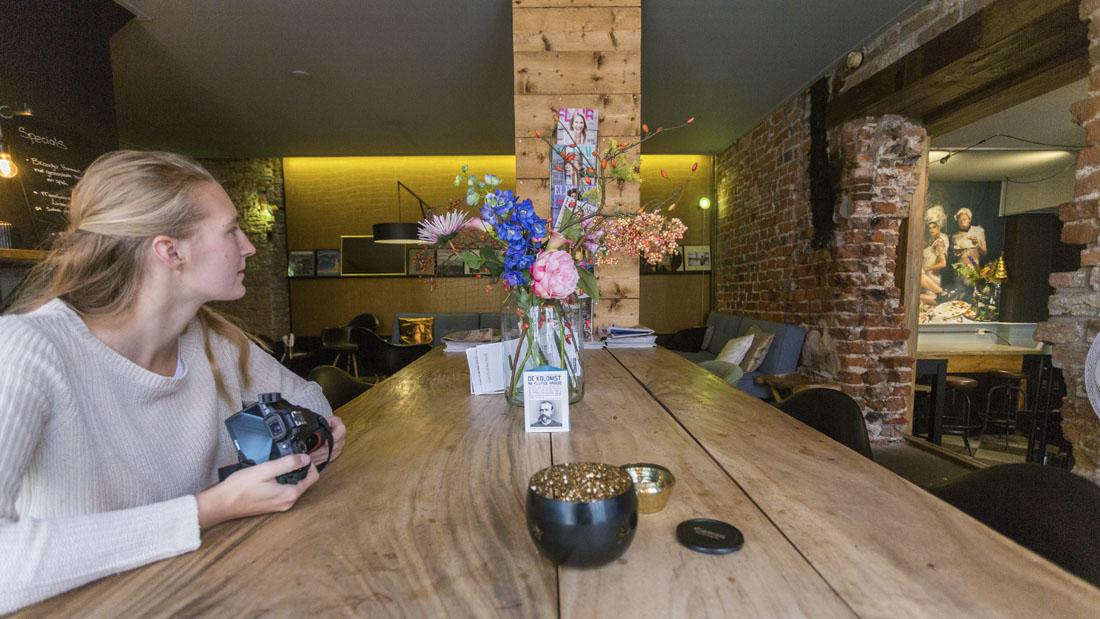 Manouk aan tafel met camera in café Laura & De Chef in Leeuwarden.