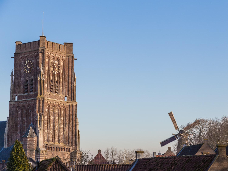 Toren van de Sint Martinuskerk in Woudrichem met een molen