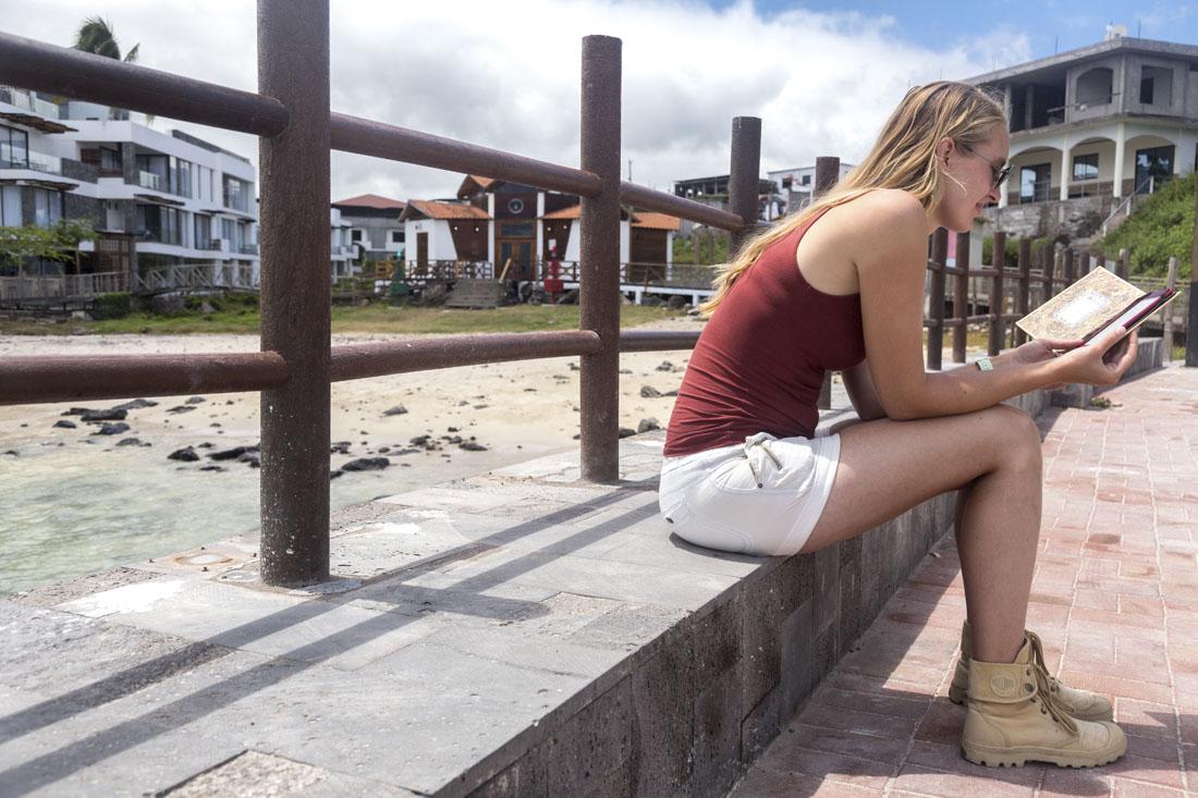 Manouk met boek in e-reader in de haven van San Cristobal op de Galapagoseilanden
