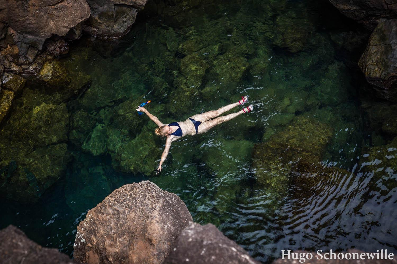 Meisje drijft in het water van Las Grietas: poelen tussen vulkanische rotsformaties op de Galápagoseilanden.