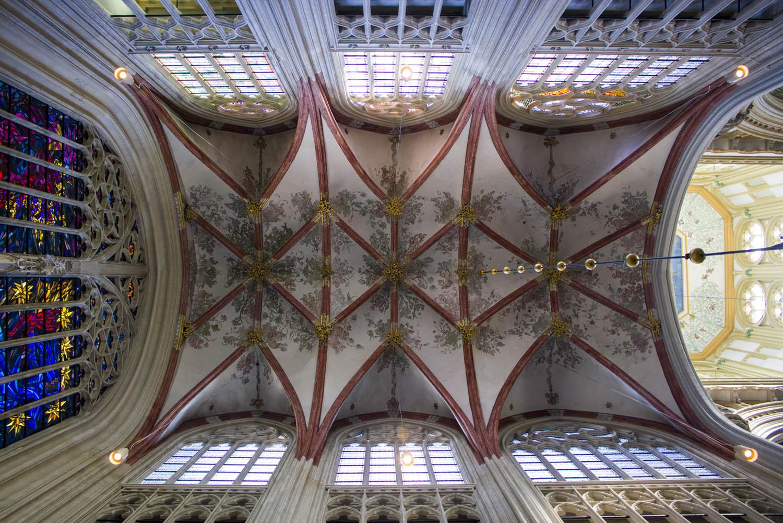 Wat te doen in Den Bosch: het rood en goud beschilderde plafond van de Sint-Janskathedraal met het immense glas-in-lood-raam.