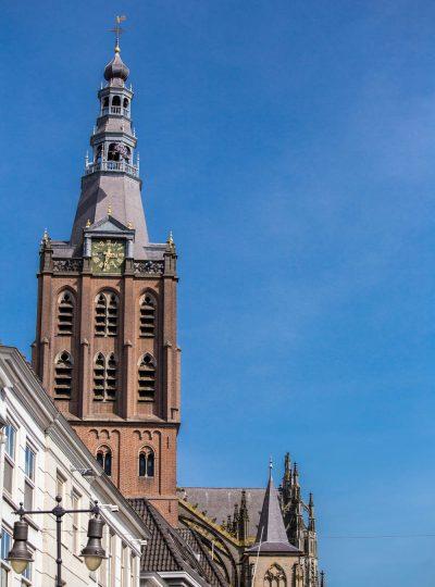 Toren van de Sint-Janskathedraal tegen een blauwe lucht