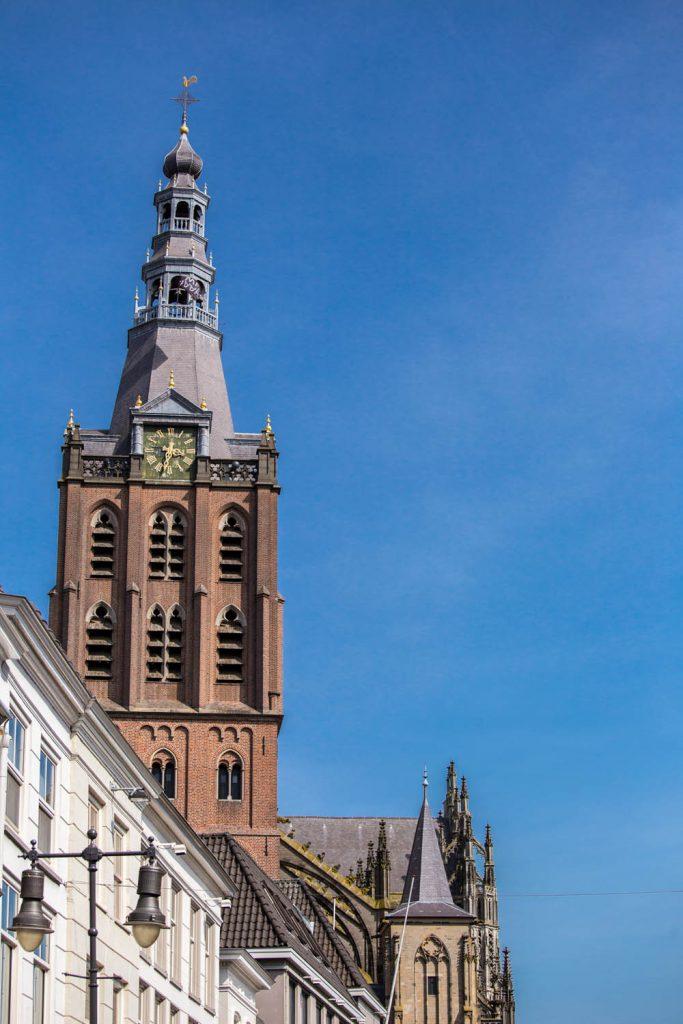 Toren van de Sint-Janskathedraal tegen een blauwe lucht.