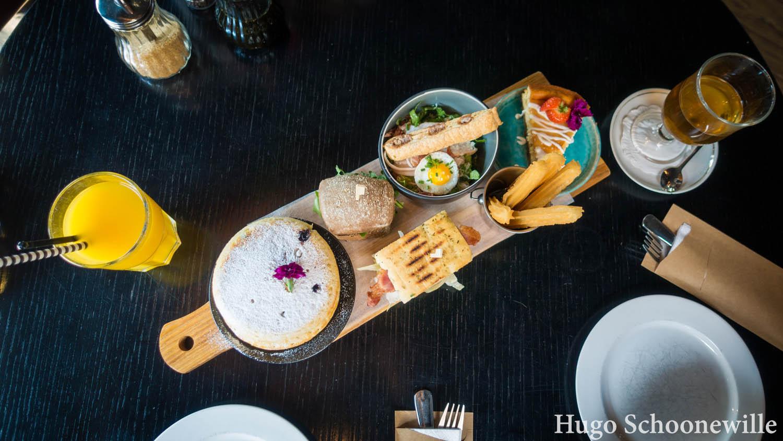 Een goedgevulde plank met allerlei brunchgerechten bij Bij Hartje Zwolle: pancakes, churros, taart en hartige broodjes.