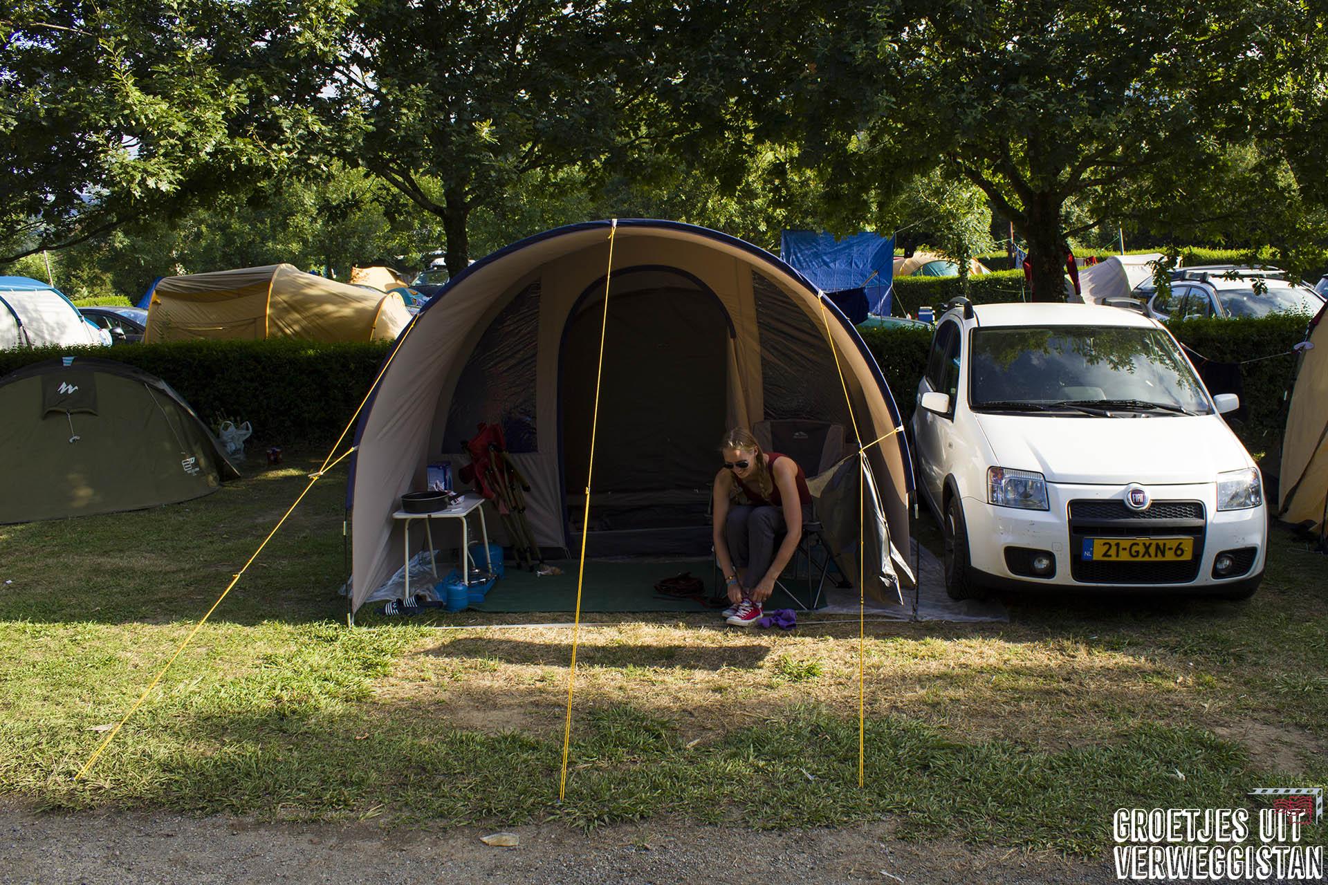 Een tent met auto op een volle camping in Spanje: wat moet er op je inpaklijst als je gaat kamperen?