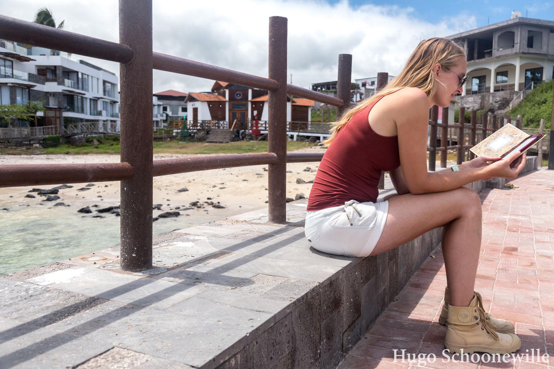 Met een e-reader zittend in de haven van Puerto Baquerizo Moreno: reizen met een e-reader is een stuk handiger.