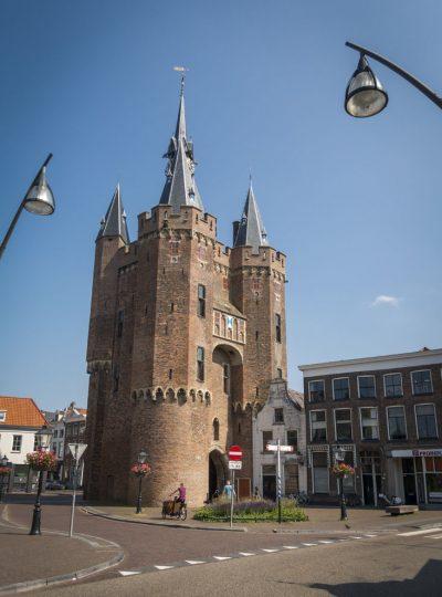 De indrukwekkende Sassenpoort, overblijfsel van de stadsmuur van Zwolle, met torens en een blauwe lucht.