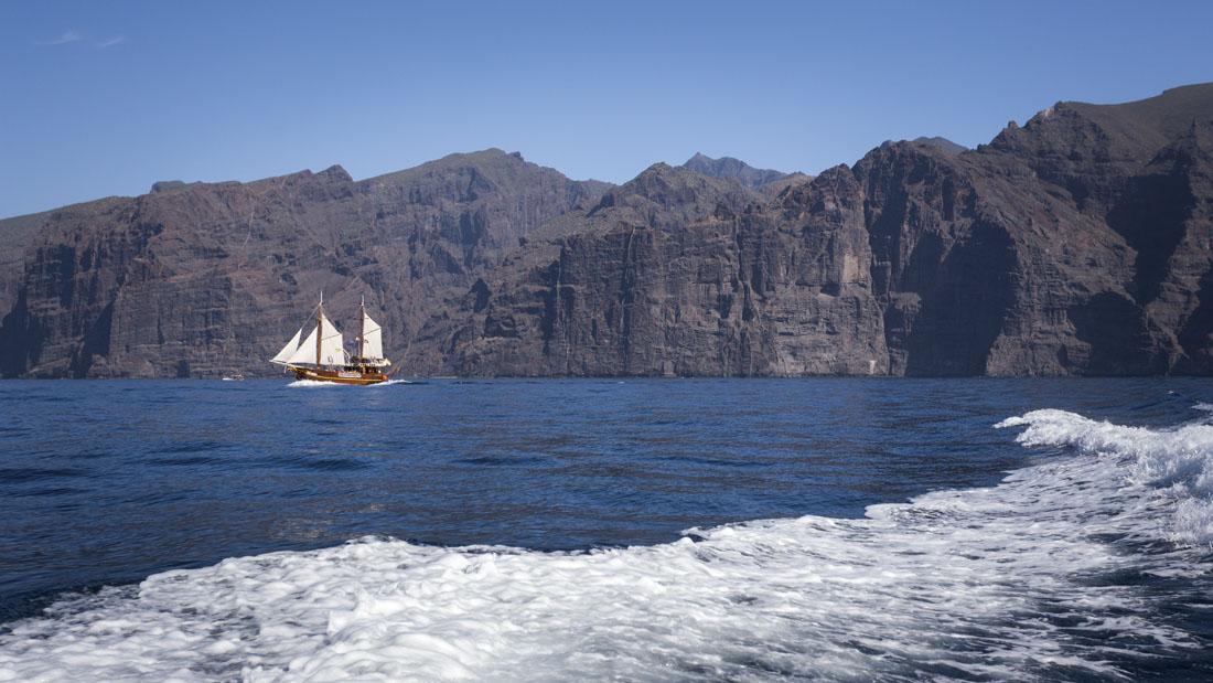 Een piratenschip met erachter de kliffen van Los Gigantes, honderden meters boven het water