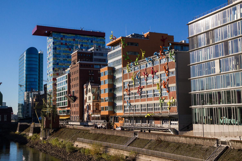 Moderne architectuur in Medienhafen in Düsseldorf: mannetjes klimmen een gebouw op.