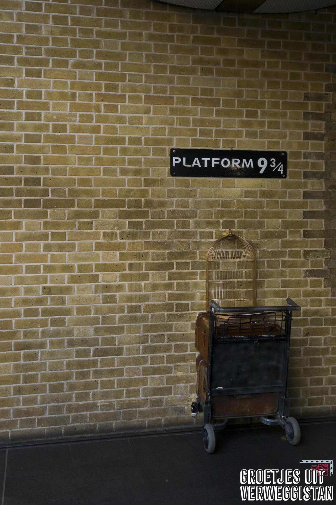De trolley en muur bij Platform 9 3/4 in King's Cross.