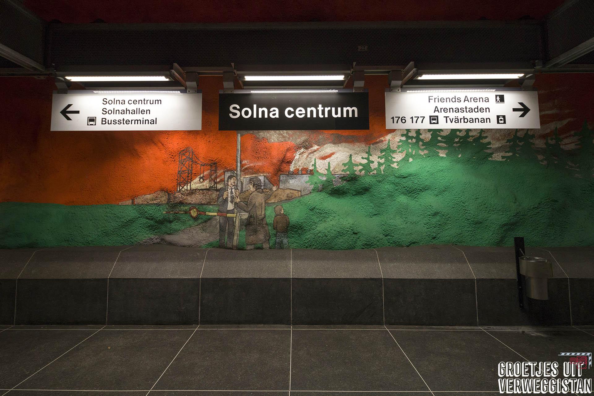 Platform van metrostation Solna Centrum in Stockholm, met metrokunst in oranje en groen.
