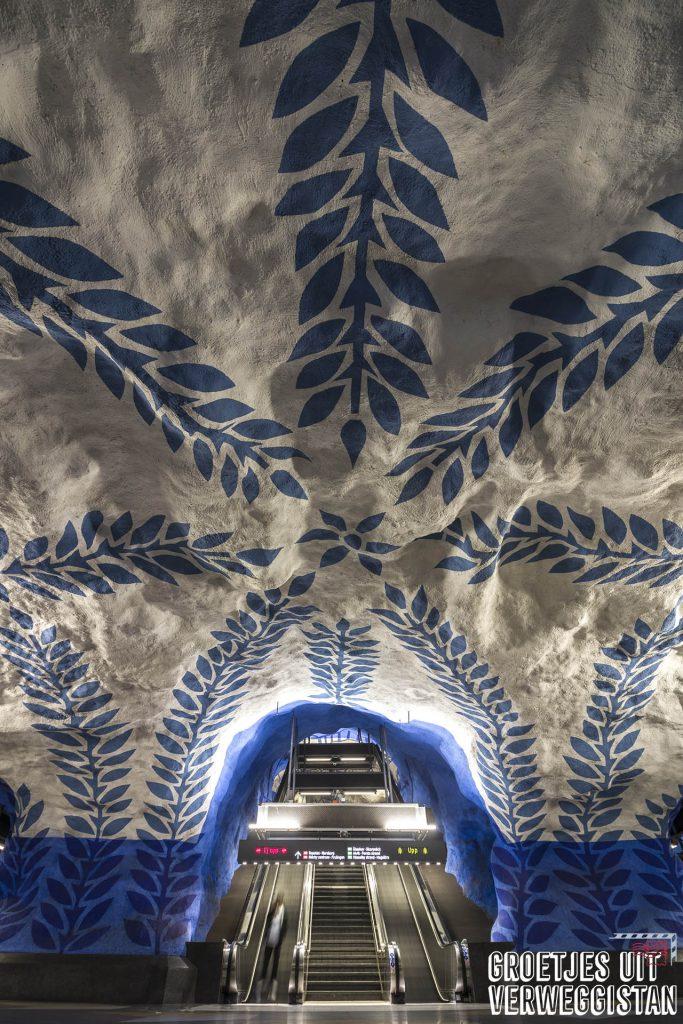 Kunst in de metro in Stockholm: wit met blauw wijnrankmotief op de muren en plafonds op het platform van de blauwe lijn van de metro in Stockholm.