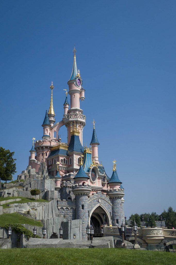 Het roze kasteel in Disneyland Parijs tegen een blauwe lucht.
