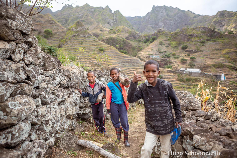 Drie jongetjes op een pad in de plantages op Kaapverdië op het eiland Santo Antão waarvan eentje een boomstam draagt.