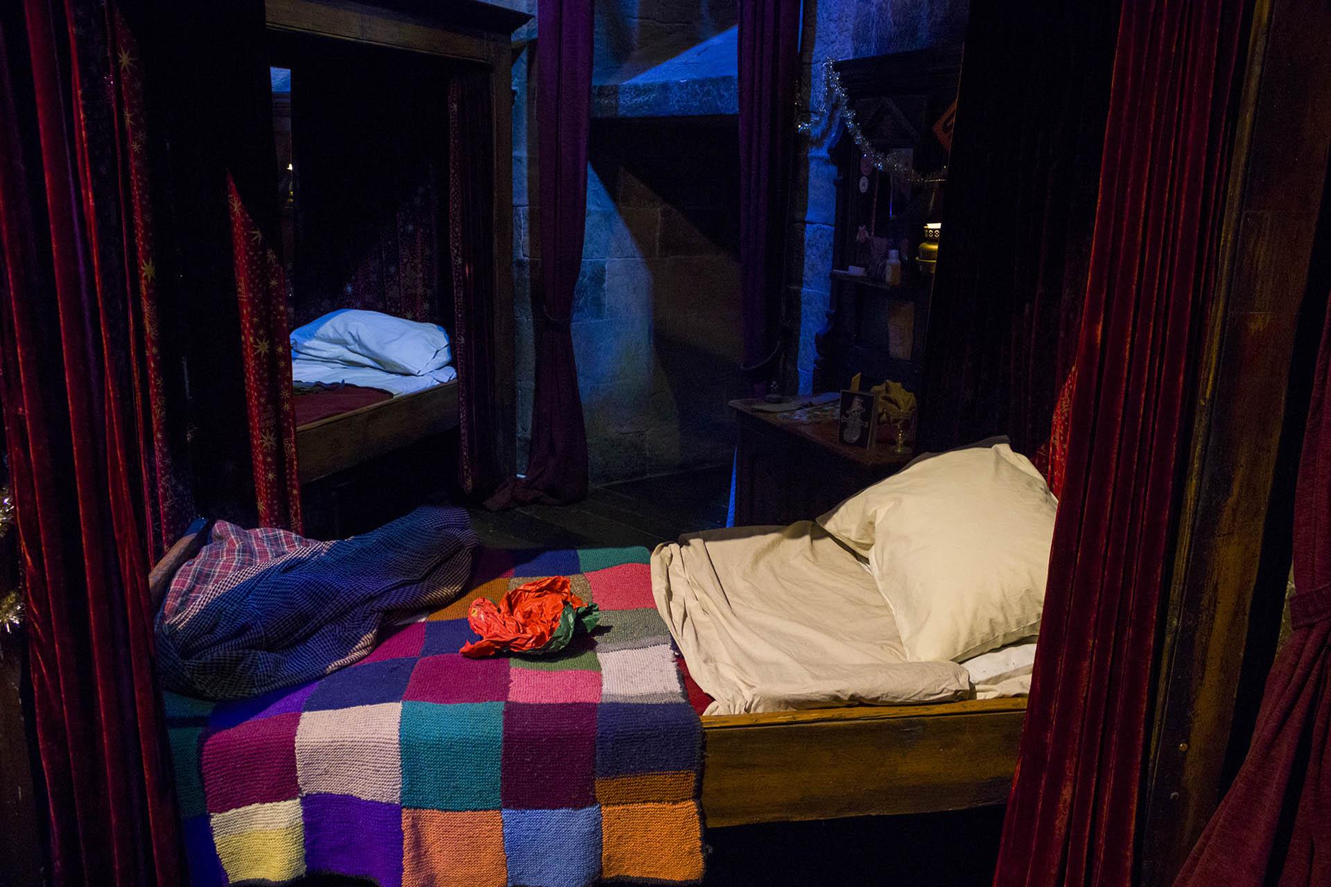 Eén van de bedden in de Gryffindor common room in de studio's met cadeaupapier van de kerstcadeaus.