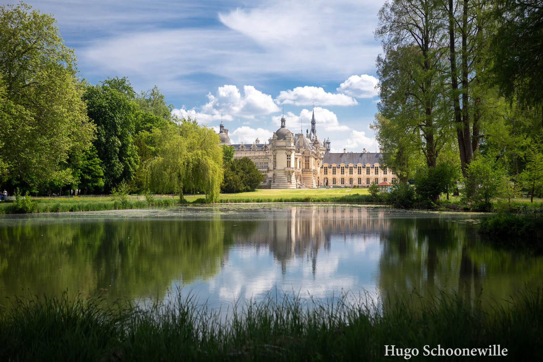 Doorkijkje naar Château de Chantilly vanuit de Engelse tuinen van het kasteel met weerspiegeling in het water.