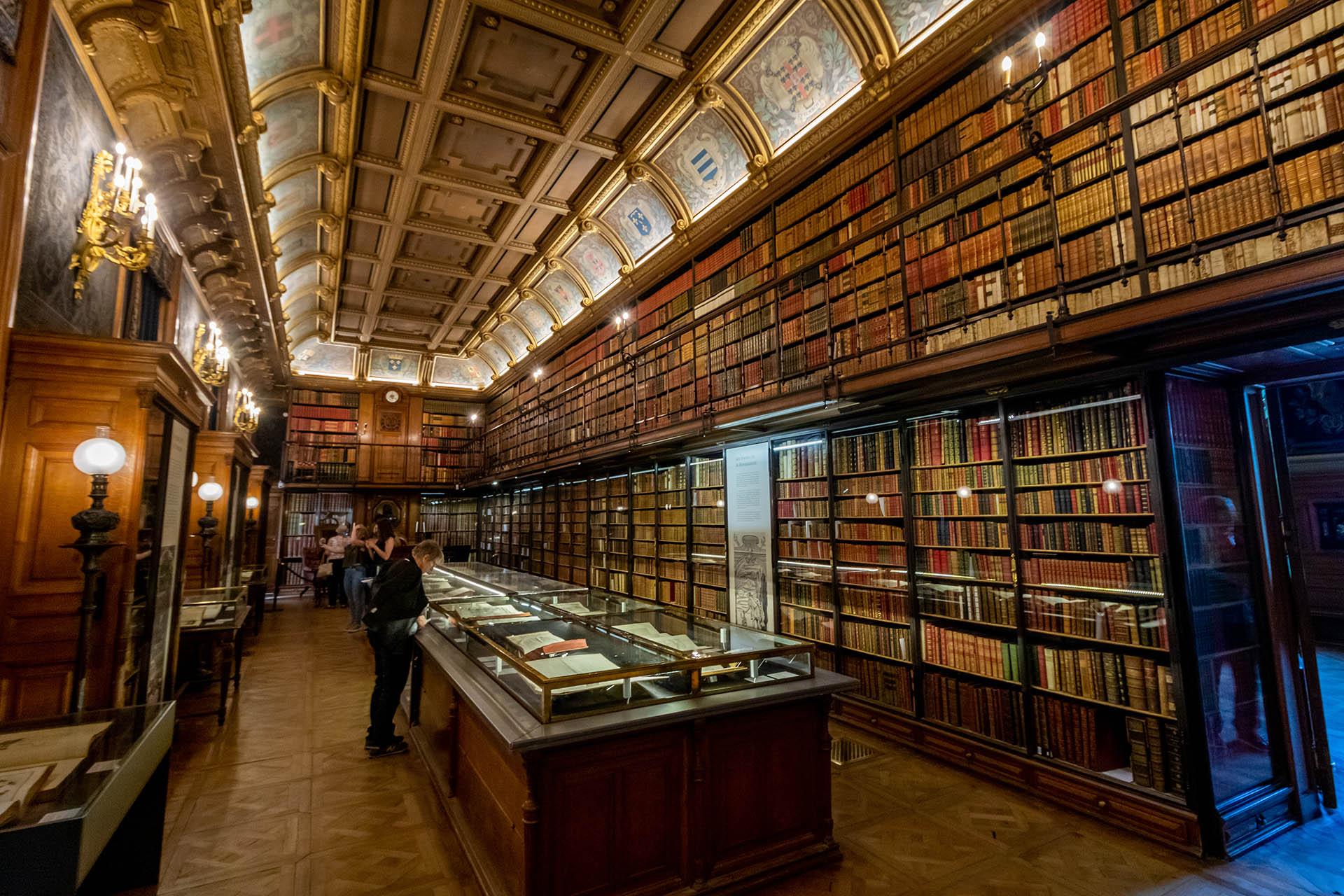 De oude bibliotheek in Château de Chantilly met een kasten vol oude boeken en een vitrine in het midden.