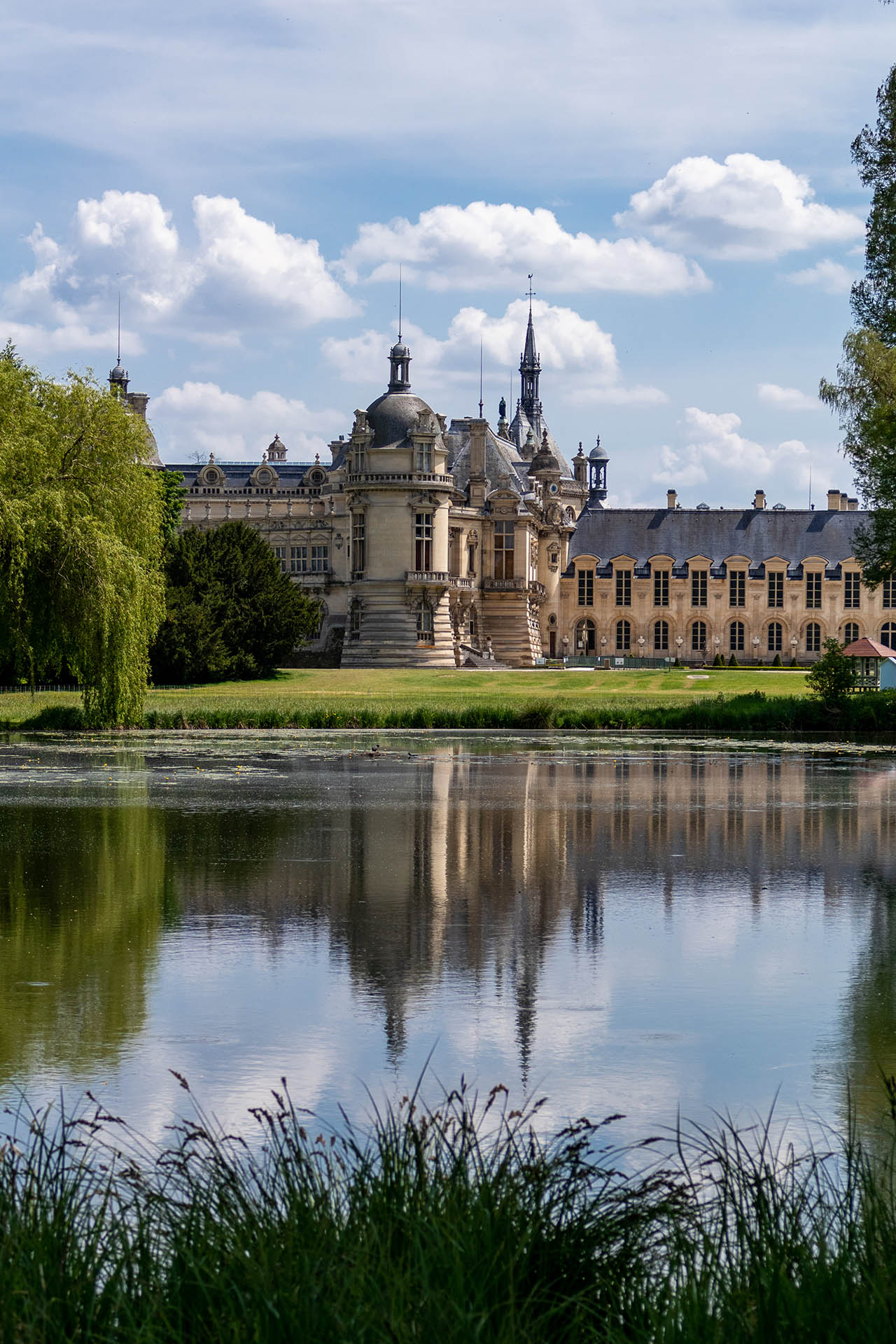 Kasteel van Chantilly met weerspiegeling in het water vanuit de Engelse tuinen.