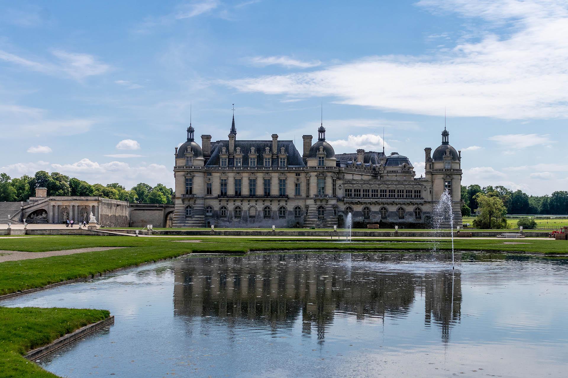 Het kasteel van Chantilly vanuit de Franse tuinen met fonteinen op de voorgrond en weerspiegeling in het water.