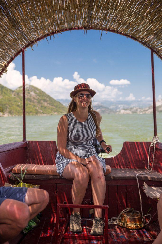 Manouk aan het roer van een houten boot met rieten dak op het Skadarmeer in Montenegro.