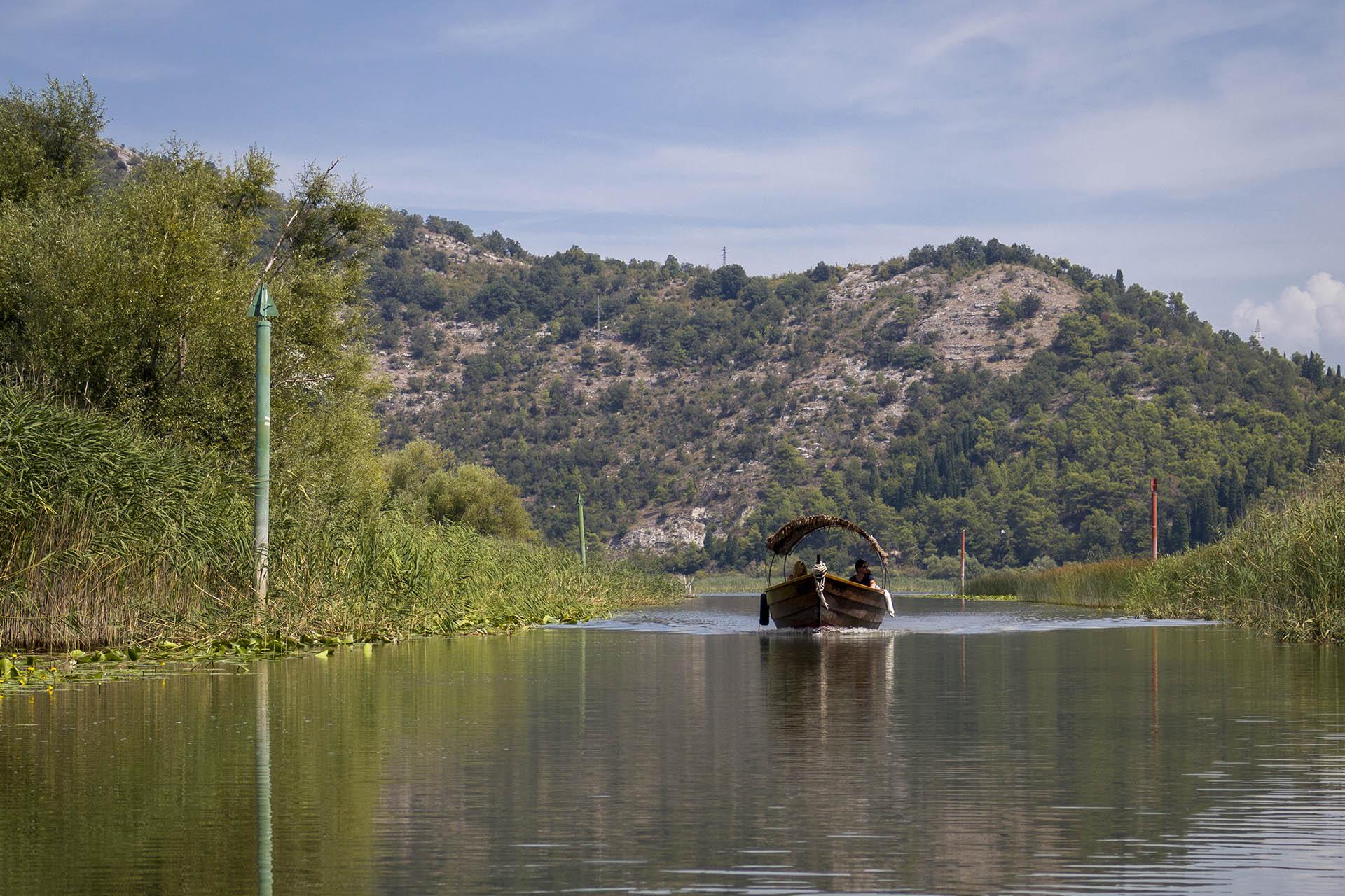 Boot met rieten dak vaart over de rivier Crmnica vanaf het Skadarmeer.
