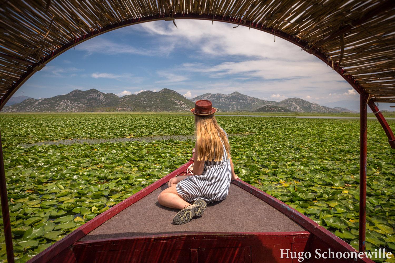 Meisje op de voorzijde van een houten boot op het Skadarmeer in Montenegro tussen de waterlelies