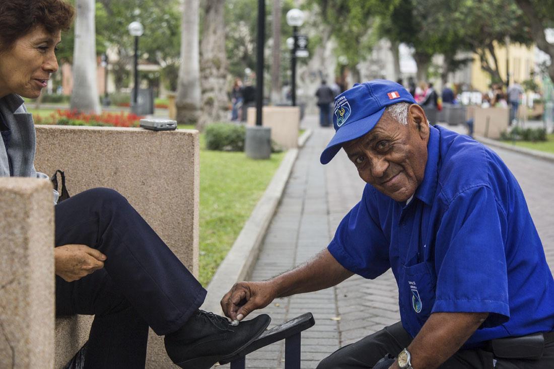 Een schoenenpoetser in Kennedy Park in Lima die een klant aan het helpen is.