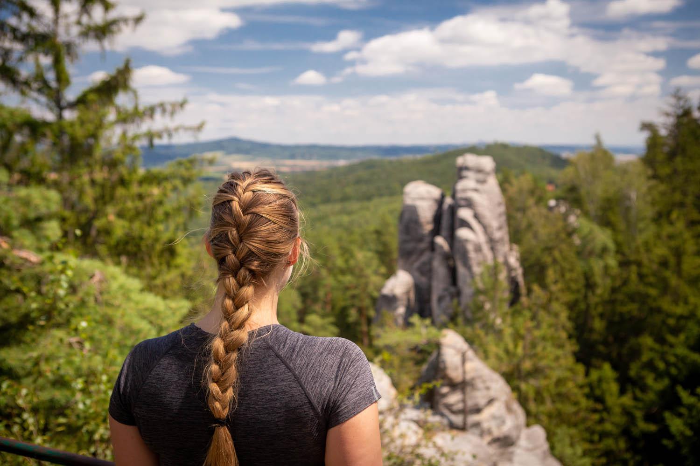 Manouk met vlecht in haar haren kijkt uit over de grijze rotspunten van de rotsen van Prachov