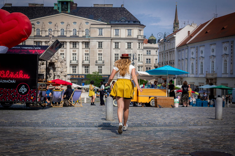 Meisje in gele rok rent richting het marktplein in Brno in Tsjechië.