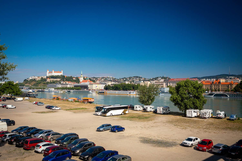 Auto's staan op gratis parkeerplaats aan het water met op de achtergrond de Donau en het kasteel van Bratislava