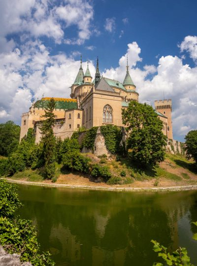 Het kasteel van Bojnice met de slotgracht, torentjes en de blauwe lucht