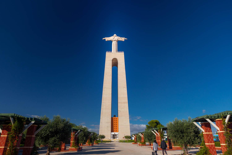 Het beeld Cristo Rei torent boven je uit op een hoge pilaar.