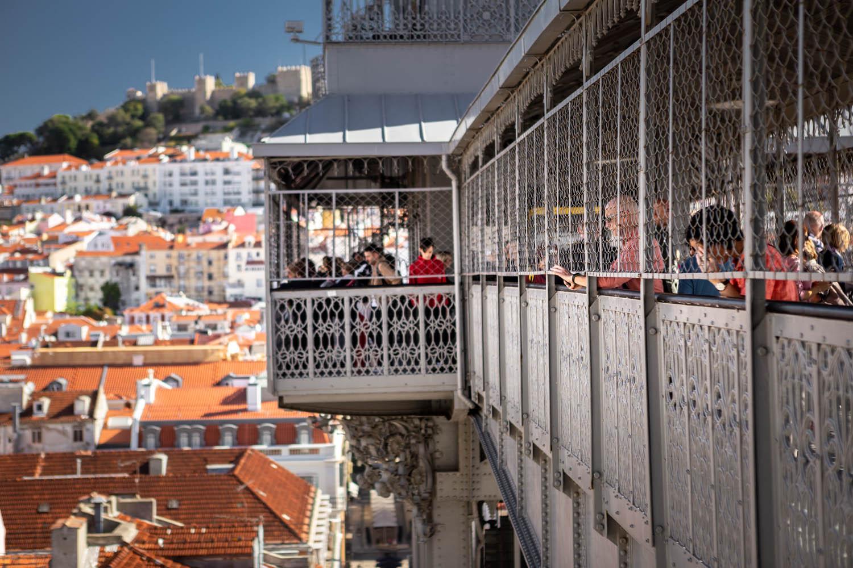 Mensen kijken uit over Lissabon vanaf boven bij Elevador de Santa Justa.