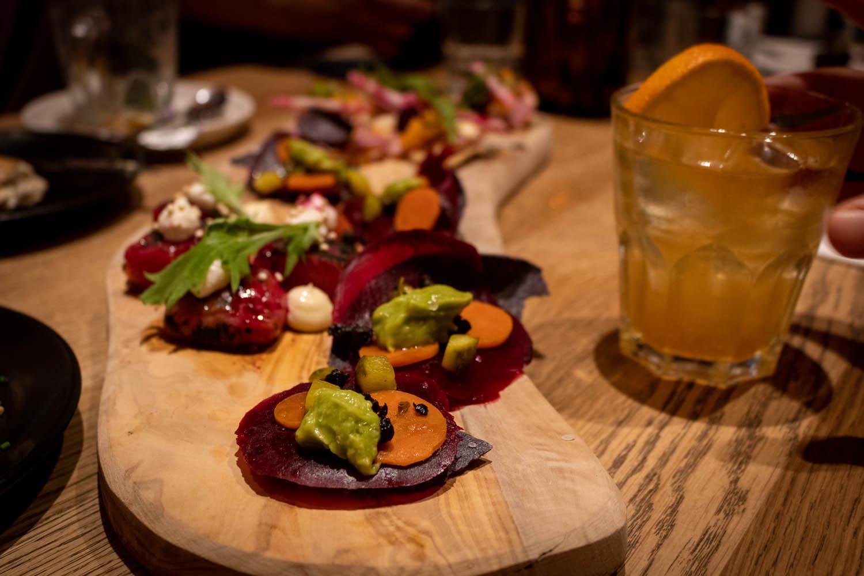 Hapjes met bieten, avocado en wortel op een borrelplank met een limonade bij STAN&CO in Den Haag.