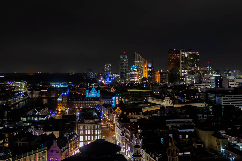 Uitzicht over Den Haag in het donker, met de moderne hoogbouw en Ridderzaal