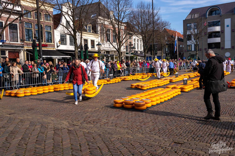 Toerist rent met kaasdragers in Alkmaar op de kaasmarkt.